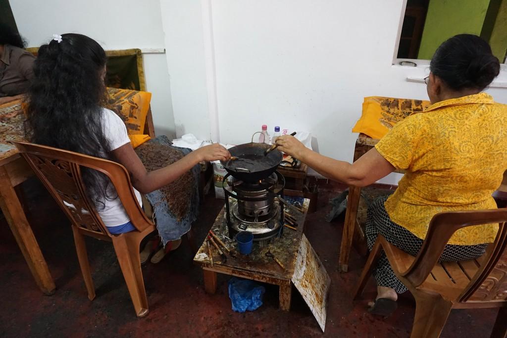 Batik-Malerinnen bestreichen Stoffe mit Wachs um die Stellen vor Verfärbung zu schützen